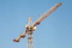Construction crane against blue sky. Stock Photos