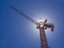 Construction crane. Against blue sky back lit by sun Royalty Free Stock Photography