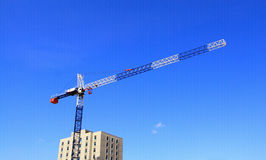 Construction crane against blue sky background. Construction crane near highrise building with blue sky background Royalty Free Stock Images