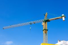 Construction crane on a background of blue sky. Construction crane building a house on a background of blue sky royalty free stock photos