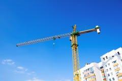 Construction crane on a background of blue sky. Construction crane building a house on a background of blue sky stock image