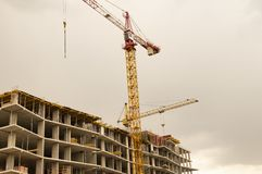 Construction crane on the background of a house under construction royalty free stock images