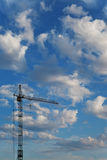 Construction crane on a background sky with clouds Stock Photos