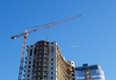 Construction crane on the background of a skyscraper under const Stock Images