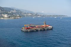 Construction crane barge. A construction crane barge begins land reclamation work off the coast of Monaco stock photography