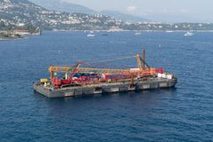 Construction crane barge. A construction crane barge begins land reclamation work off the coast of Monaco royalty free stock photography