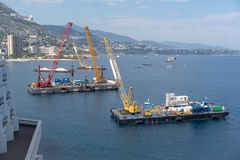 Construction crane barges. A construction crane barges begins land reclamation work off the coast of Monaco stock image