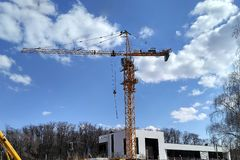 The construction crane and the building against the blue sky royalty free stock photo