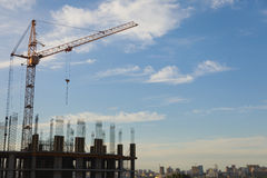 The construction crane and the building against the blue sky Royalty Free Stock Photos