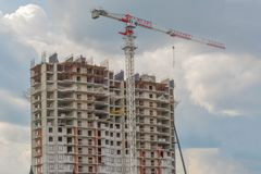 Construction crane and building under construction against blue sky royalty free stock image