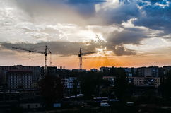 Construction crane cityscape at sunset sky background Stock Images