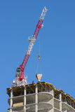 Construction crane. Delivers the concrete to build a house Stock Photography