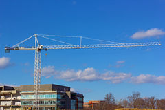 Construction crane high above new building. Royalty Free Stock Photo