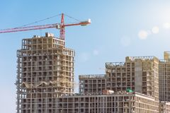 Construction crane and high-rise buildings, property sales for the population stock photos