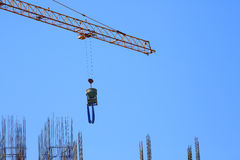 Construction crane hoisting cement bucket Royalty Free Stock Images