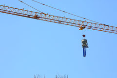 Construction crane hoisting cement bucket mixer Royalty Free Stock Images