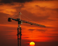 Construction Crane Hoisting the Sun Royalty Free Stock Image