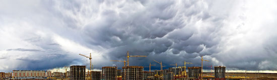 Construction crane industrial concrete skyscraper storm rain weather sky panorama Royalty Free Stock Photos