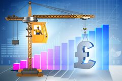 Construction crane lifting british pound in currency business co Stock Photos