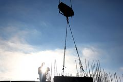 Construction crane lifts the load against the sun royalty free stock image