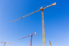Construction Crane Machines. Building construction site crane hoisting rigging machines high structures  in blue sky Stock Images