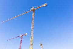 Construction Crane Machines. Building construction site crane hoisting rigging machines high structures  in blue sky Stock Photo