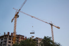 Construction crane moving down building structure Royalty Free Stock Image