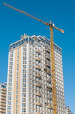 Construction crane and multi-storey building. Yellow tower crane on a background of a new high-rise building Royalty Free Stock Photo