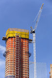 Construction - Crane and new highrise apartment building Stock Images