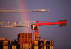 Construction crane and rainbow. The elevating crane of construction on a background of the dark blue sky and a rainbow Royalty Free Stock Photography