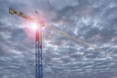 Construction crane, ray of light in background. Stock Images