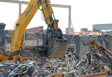 Construction Crane Removing the trash remains from a Demolished Building Stock Image