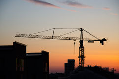 Construction crane by roofs at sunrise Royalty Free Stock Photo