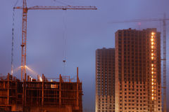 Construction crane on the site, unfinished multi-storey houses, fog covers the upper floors, evening twilight Stock Photography