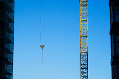 Construction crane on the sky background among buildings Stock Image