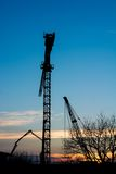 Construction crane at sunset. Stock Photos