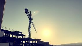 Construction crane time lapse. Time lapse of construction crane moving over unfinished building in contre-jour with sun moving in the frame stock video footage