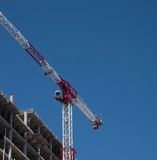 Construction crane towering over an unfinished building Royalty Free Stock Photo