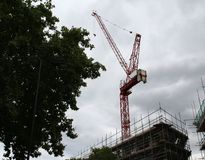 Construction crane towers on cloudy sky with some background. Great for under contractions web page stock photography