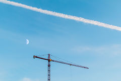 Construction crane, trace of airplane and moon Royalty Free Stock Image