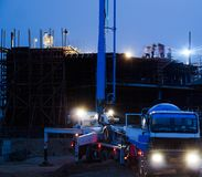 Construction crane truck working on structure at night Royalty Free Stock Images