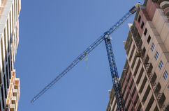 Construction crane between two houses Royalty Free Stock Images