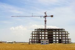Construction crane and unfinished building. High construction crane and unfinished building. Mountains and blue sky on background Royalty Free Stock Photo