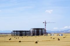 Construction crane and unfinished building. High construction crane and unfinished building. Mountains and blue sky on background Stock Photo