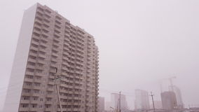 Construction crane and unfinished house in the fog. Steadicam shot stock video footage