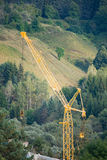 Construction crane working in the woods in summer Royalty Free Stock Image
