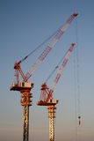 Construction Cranes. Two cranes used for skyscraper construction at sunset stock photo