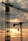Construction Cranes. Silhouettes of Construction Cranes at sunset stock photos