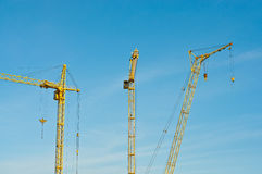 Construction cranes. Tall tower cranes on construction site Stock Images