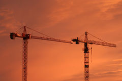 Construction cranes. In Tallinn  silhouetted against a fiery sunset Royalty Free Stock Photos